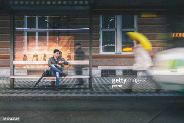 man on the bus stop on a rainy night - waiting stock pictures, royalty-free photos & images