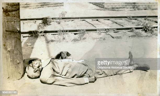 Man on the ground beside train tracks following the Tulsa Race Massacre, Tulsa, Oklahoma, June 1921.