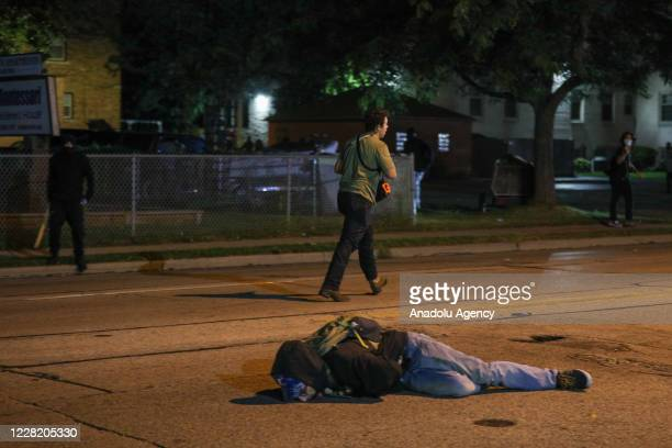 Man on the ground was shot in the chest as clashes between protesters and armed civilians who protect the streets of Kenosha against the arson during...