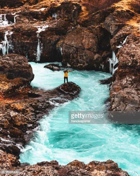 man on the iceland hraunfossar waterfalls