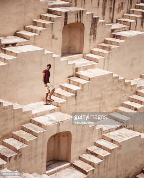 man on the infinity steps in india - jaipur - stepwell stock pictures, royalty-free photos & images