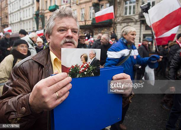Man on the march of freedom and solidarity organized by the ruling party Law and Justice in Warsaw carries a photo of Polish presidential couple Lech...