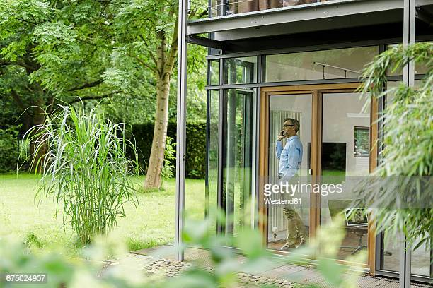 Man on the phone in his house looking through window