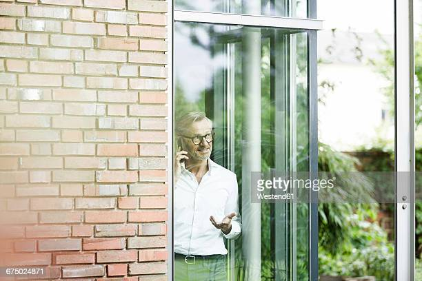 Man on the phone looking through window