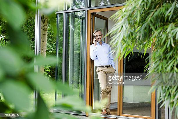 man on the phone standing at open door of his house - only mature men stock pictures, royalty-free photos & images