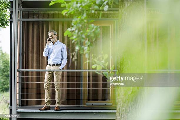 man on the phone standing on balcony of his house - only mature men stock pictures, royalty-free photos & images