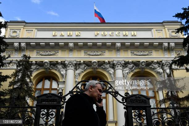 Man on the phone walks past the Russian Central Bank headquarters as the Russian flag flies, in downtown Moscow, on March 19, 2021. - Russia's...