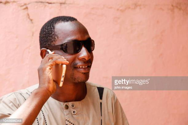a man on the phone with black glasses - mali photos et images de collection