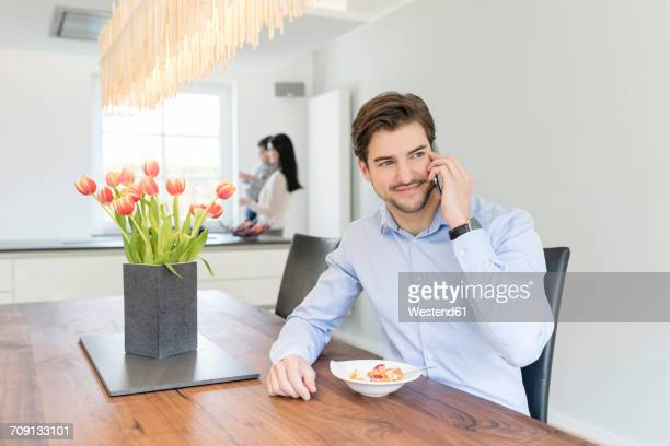 Man on the phone with mother and son in background