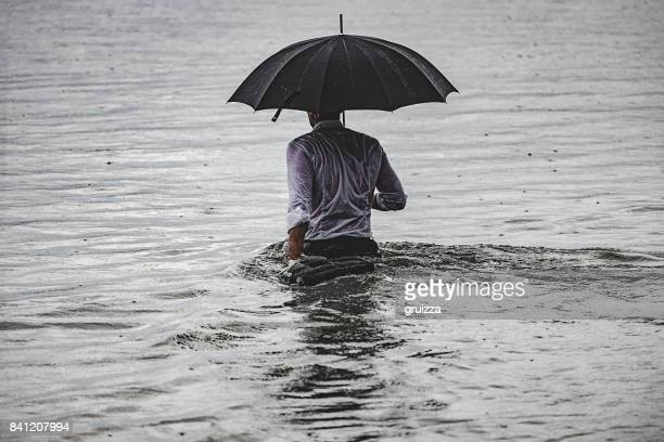 man on the rain - torrential rain stock pictures, royalty-free photos & images