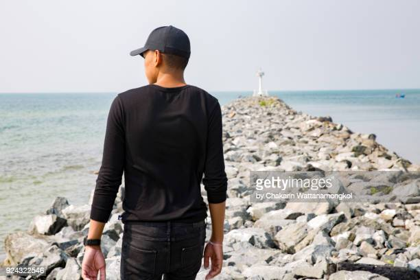 a man on the rocky path by the sea. - manches longues photos et images de collection