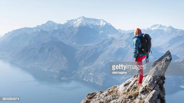 man on the top of the mountain peak - escapism stock photos and pictures