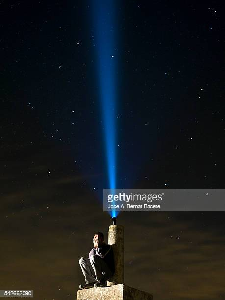 Man on top of a mountain, desperate hands on the lost face at night with a flashlight signal
