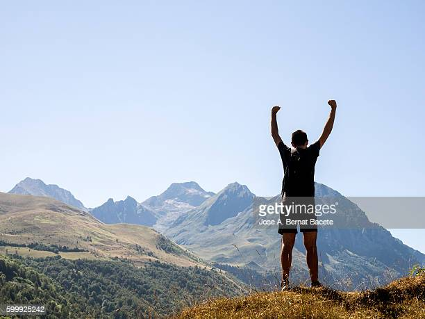 Man on top of a mountain with arms outstretched as a symbol of victory