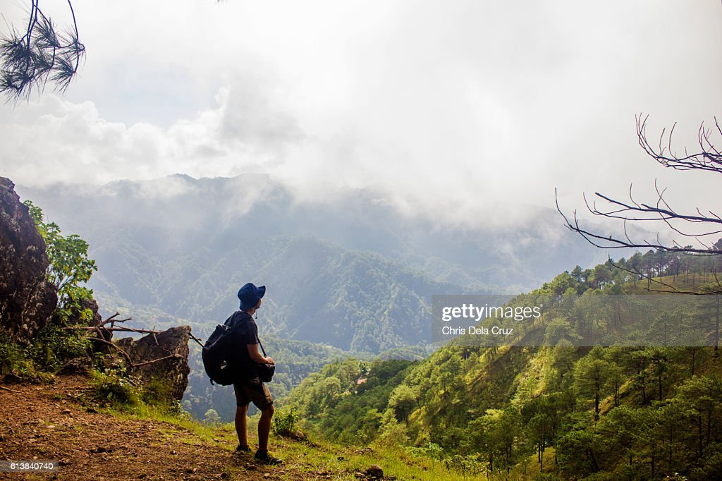 Man on top of a mountain with warm trees and cloudy sky : Stock Photo