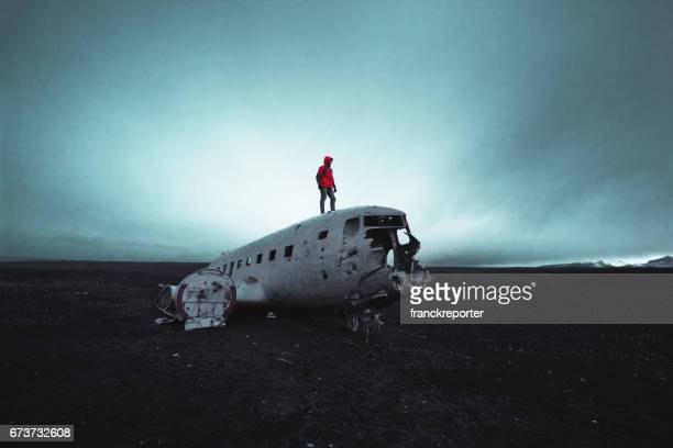 man on top of a plane wreck in iceland