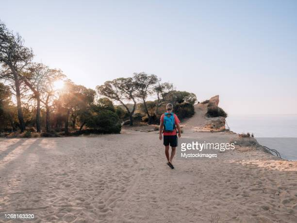 man on top of cliff in walking on the coastline - portugal stock pictures, royalty-free photos & images