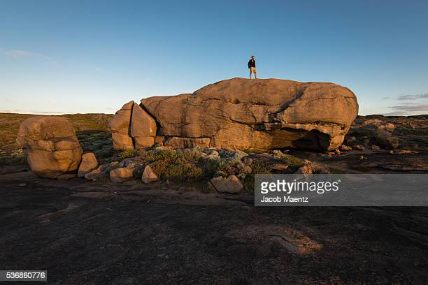 Man on top of giant rock
