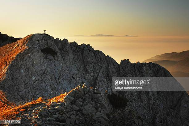 man on top of mountain cliff - middlebare afstand stockfoto's en -beelden