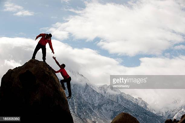Man on top of mountain helping someone up