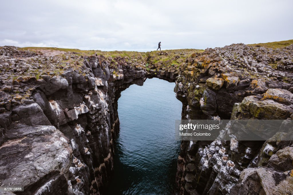 Man on top of natural rocky arch, Snaefellsnes, Iceland : Stock-Foto