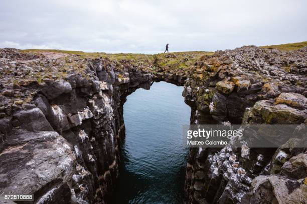man on top of natural rocky arch, snaefellsnes, iceland - geologi bildbanksfoton och bilder