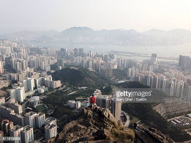 Man on top of peak with city in background