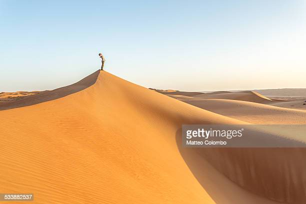 Man on top of sand dune in the desert rejoicing