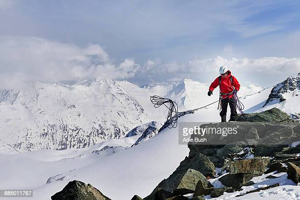 Man on top of snow covered mountain throwing climbing rope, Saas Fee, Switzerland