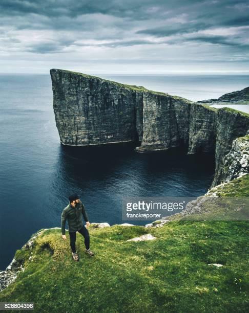 hombre en lo alto del acantilado en Islas Feroe