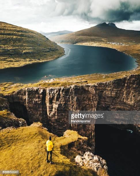 mann oben auf der klippe in färöer inseln - dramatische landschaft stock-fotos und bilder