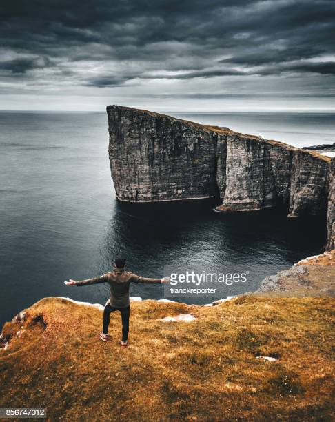 man on top of the rock at the faroe islands