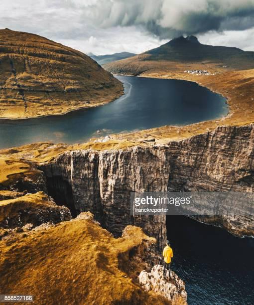 man op de top van de rots op de Faeröer