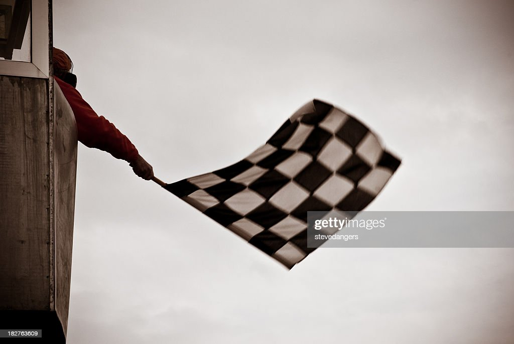 Man on tower waving checkered flag : Stock Photo