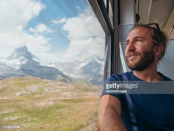 mann im zug in zermatt, schweiz - pinnacle peak stock-fotos und bilder