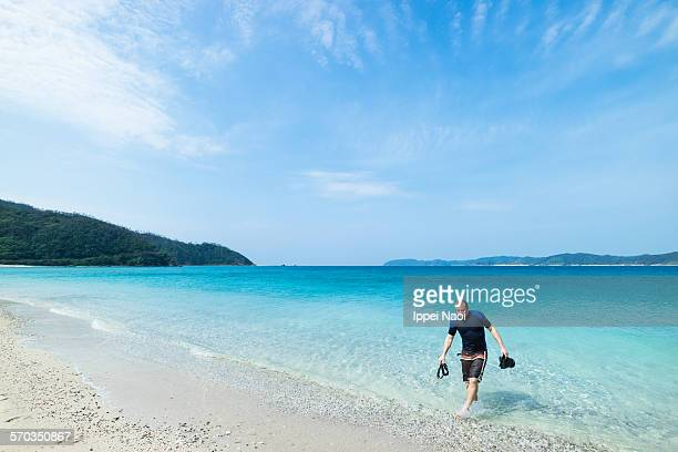 Man on tropical beach with snorkeling gear