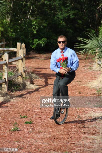 man on unicycle delivering flowers - con man stock pictures, royalty-free photos & images