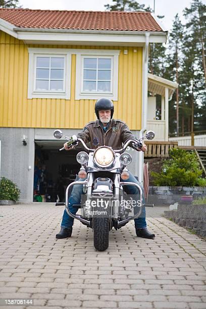 Man on vintage motorbike in driveway