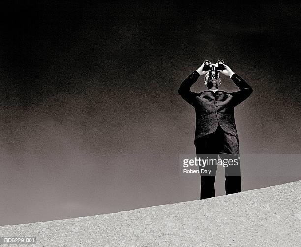 Man on wall using binoculars (B&W)