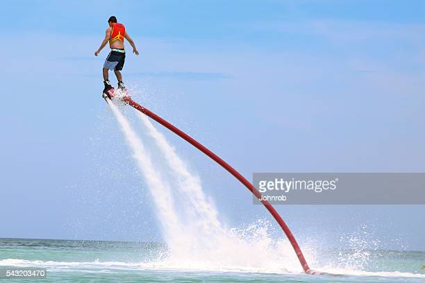 Man on water shoes jet pack in mid air Flyboarding