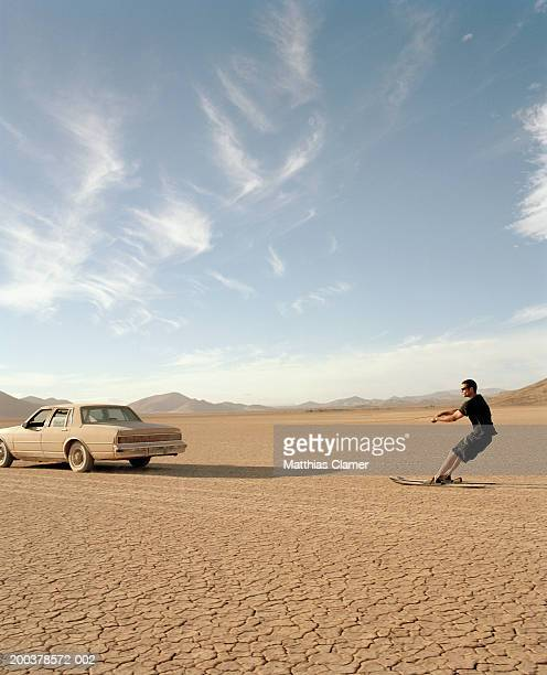 man on water skis being pulled by car in desert, side view - lake bed stock pictures, royalty-free photos & images
