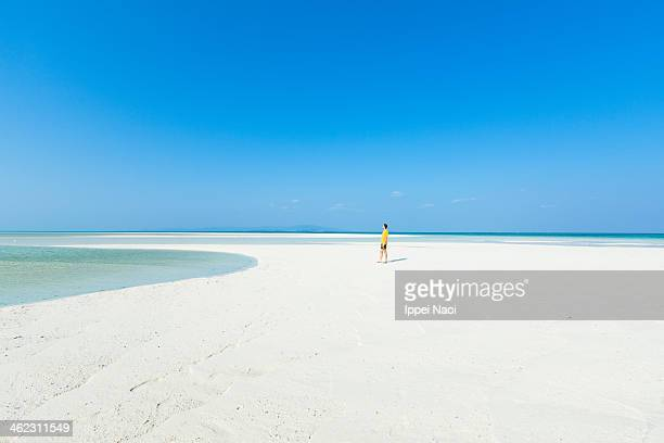 Man on white sandy tropical beach on coral cay