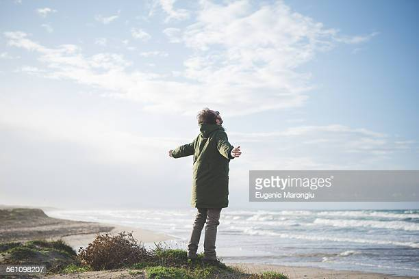 Man on windy dunes with arms open, Sorso, Sassari, Sardinia, Italy