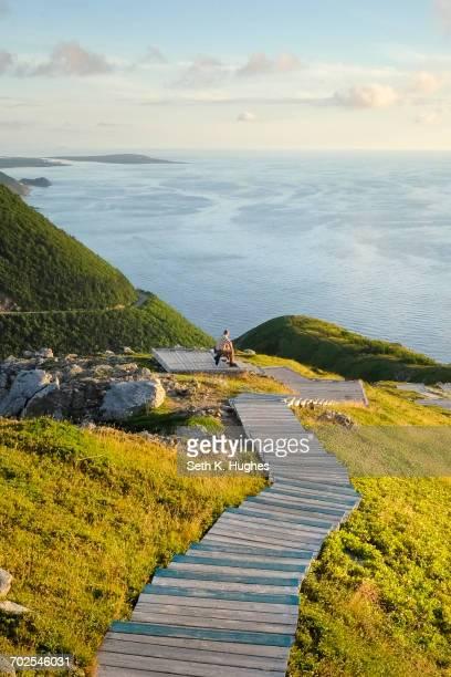 Man on wooden steps by sea, Cape Breton, Nova Scotia, Canada