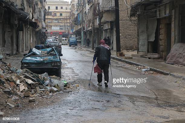 A man one of civilians stuck in alMashhad neighborhood walks with crutches through a street to reach the area where the evacuation of the civilians...