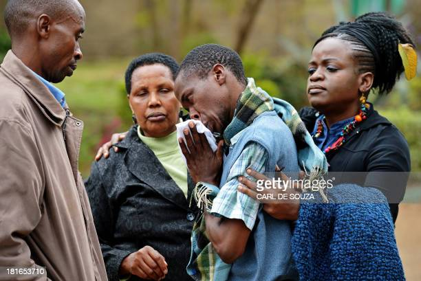 A man only identified by his first name Stephen is comforted by Pastor Elizabeth Akinyi and family members at the city mortuary in Nairobi on...
