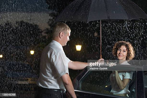 A man opening a car door and holding an umbrella over a woman