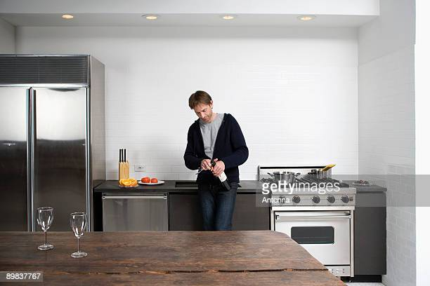 Man opening bottle of wine in the kitchen