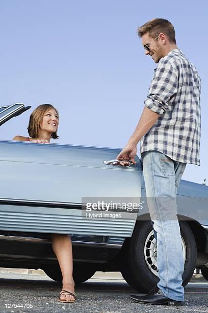 Man opening car door for girlfriend