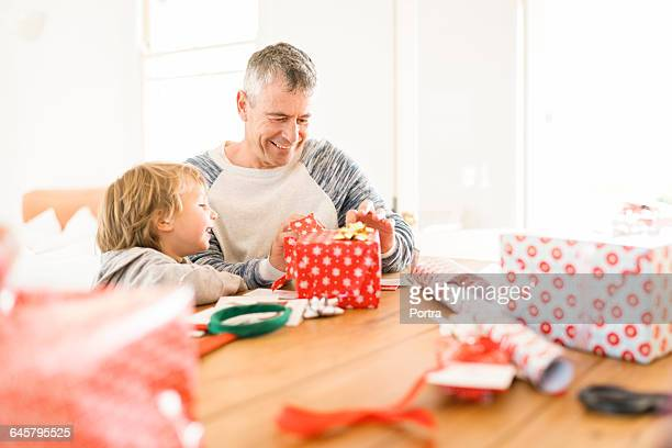Man opening Christmas gift while sitting by son